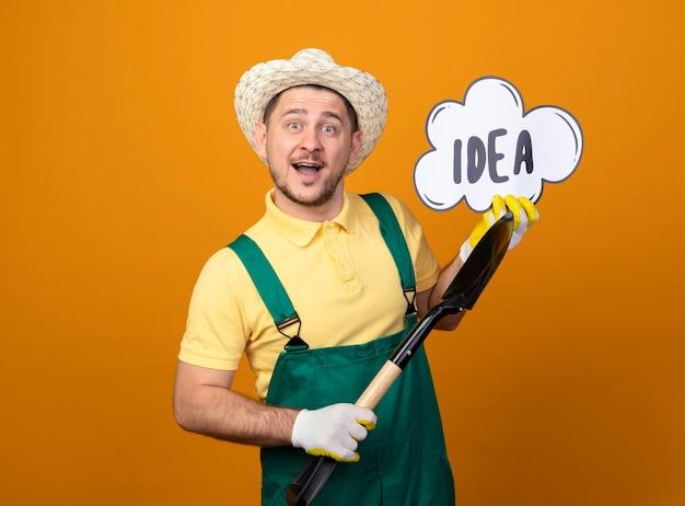 Jonge tuinman man in jumpsuit en hoed met schop en tekstballon bord met woord idee lachend met blij gezicht Gratis Foto
