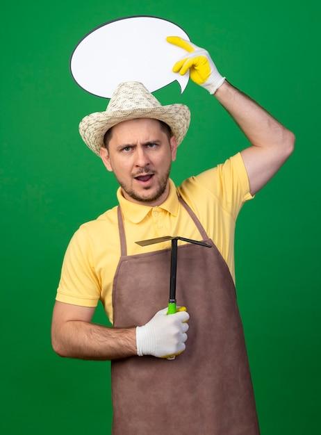 Jonge tuinman man met jumpsuit en hoed in werkhandschoenen met mattock en lege tekstballon teken boven zijn hoofd met ernstig boos gezicht Gratis Foto