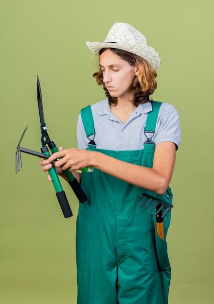 Jonge tuinman man met jumpsuit en hoed met heggenschaar Gratis Foto