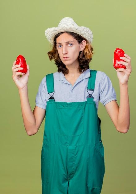 Jonge tuinman man met jumpsuit en hoed met rode paprika Gratis Foto