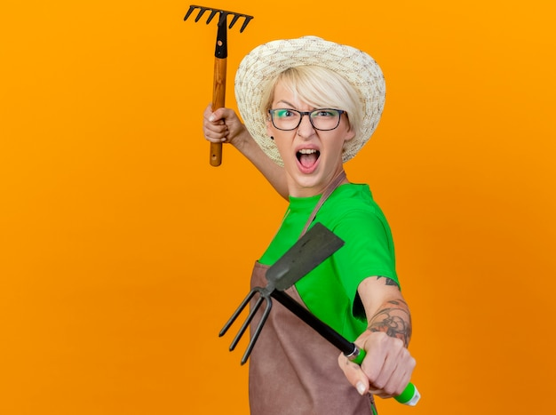 Jonge tuinman vrouw met kort haar in schort en hoed met mattock en mini hark kijken camera met boos gezicht schreeuwen staande over oranje achtergrond Gratis Foto