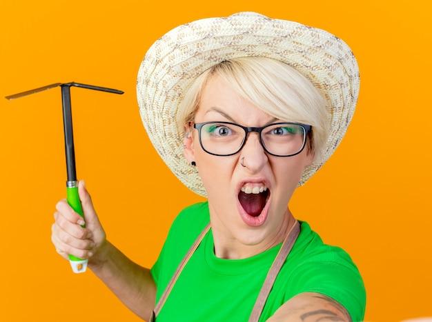 Jonge tuinman vrouw met kort haar in schort en hoed swingende mattock schreeuwen met boos gezicht gefrustreerd staande over oranje achtergrond Gratis Foto