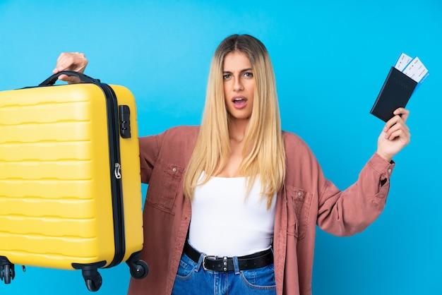 Jonge uruguayaanse vrouw over geïsoleerde blauwe muur ongelukkig in vakantie met koffer en paspoort Premium Foto