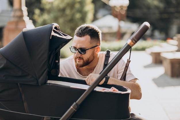 Jonge vader die met zijn baby in een kinderwagen loopt Gratis Foto