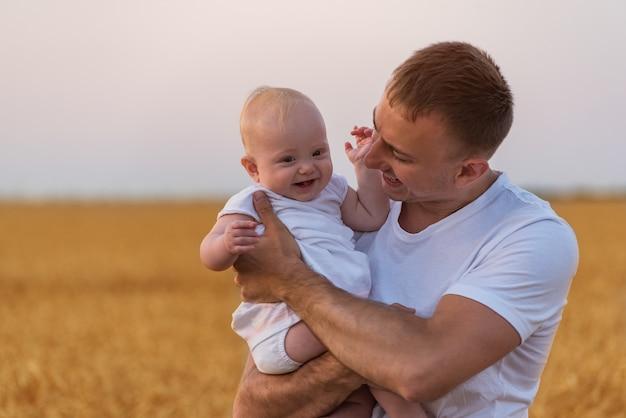 Jonge vader die schattige baby teder in zijn armen houdt. Premium Foto