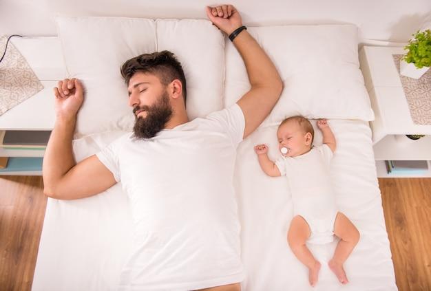 Jonge vader met een baby in het bed thuis. Premium Foto
