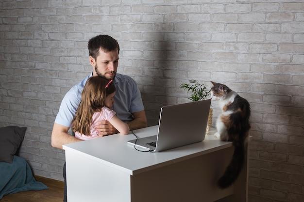 Jonge vader zit aan een tafel met een laptop en een klein kind. meisje dat met vader de monitor bekijkt Premium Foto
