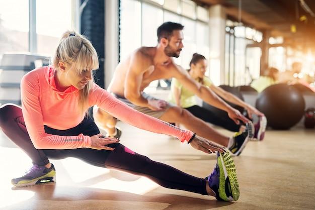 Jonge vermoeide atleten in een gymnastiek die hun beenspieren na pilatesklasse uitrekken. Premium Foto