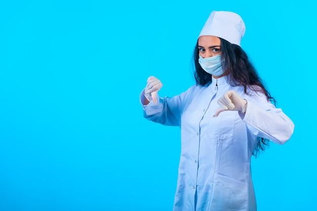 Jonge verpleegster in geïsoleerd uniform bedrijf dat duim omlaag handteken maakt Gratis Foto