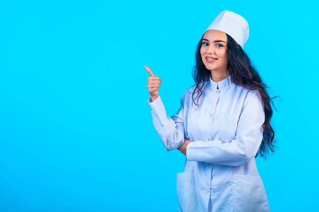 Jonge verpleegster in geïsoleerd uniform ziet er opgewekt uit en maakt een positief teken Gratis Foto