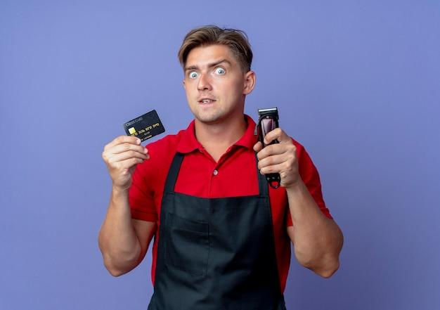 Jonge verrast blonde mannelijke kapper in uniform houdt creditcard en haartrimmer geïsoleerd Gratis Foto