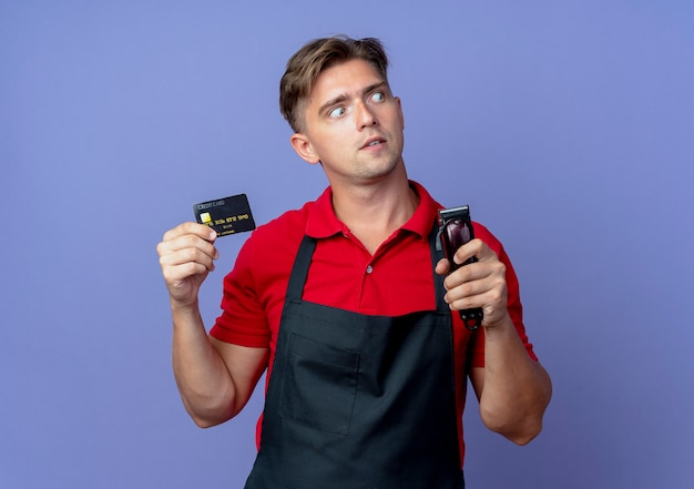 Jonge verrast blonde mannelijke kapper in uniform houdt creditcard en haartrimmer Gratis Foto