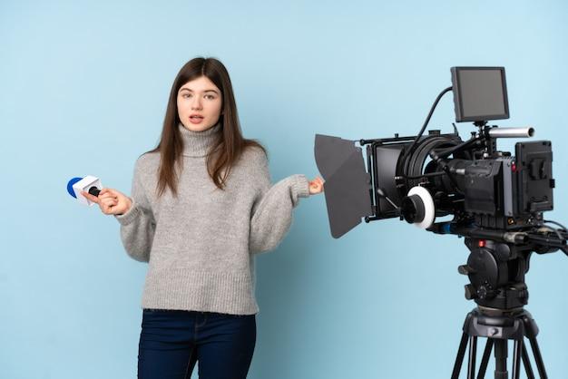 Jonge verslaggeversvrouw die een microfoon houdt en nieuws rapporteert dat op de zijtakken twijfels heeft Premium Foto