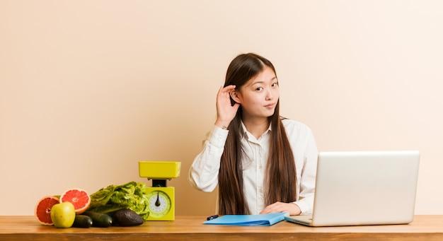 Jonge voedingsdeskundige chinese vrouw die met haar laptop werkt die aan het luisteren van een roddel probeert. Premium Foto