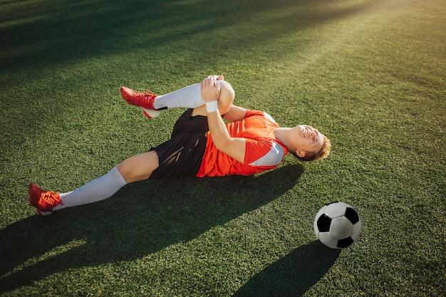 Jonge voetballer liggend op het gazon en houd been. hij trekt het naar zich toe. guy voelt pijn in de knie. bal die naast hem ligt. Premium Foto