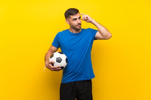 Jonge voetballermens die twijfels en met verwarde uitdrukking hebben Premium Foto