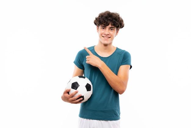 Jonge voetballermens over geïsoleerde witte muur die aan de kant richt om een product te presenteren Premium Foto
