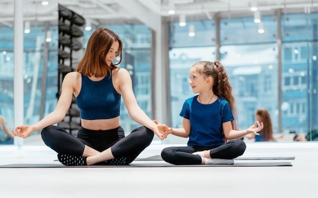 Jonge volwassen moeder en dochtertje samen beoefenen van yoga Gratis Foto
