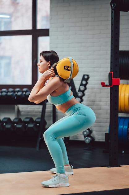 Jonge volwassen vrouw die krachtoefeningen in de gymnastiek doet Gratis Foto
