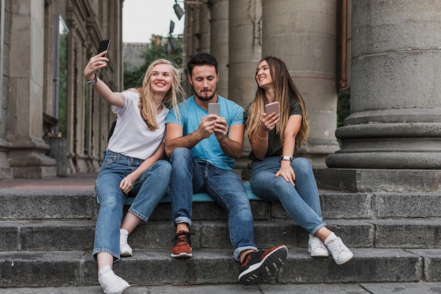 Jonge vrienden die op treden zitten en een selfie nemen Gratis Foto