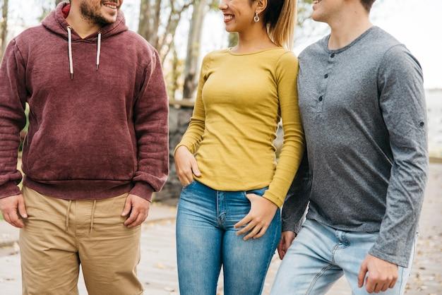 Jonge vrienden die terwijl het lopen in vrijetijdskleding glimlachen Gratis Foto