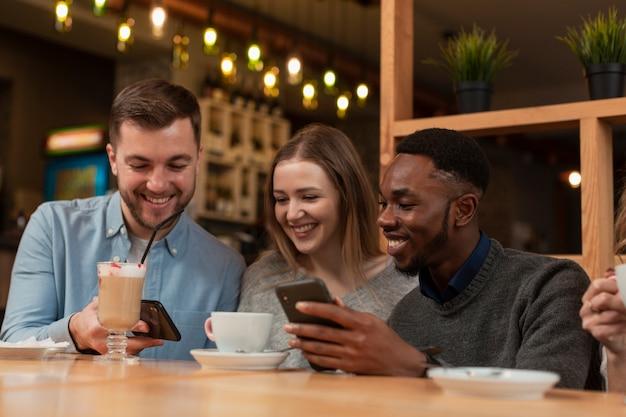 Jonge vrienden met behulp van telefoons in restaurant Gratis Foto