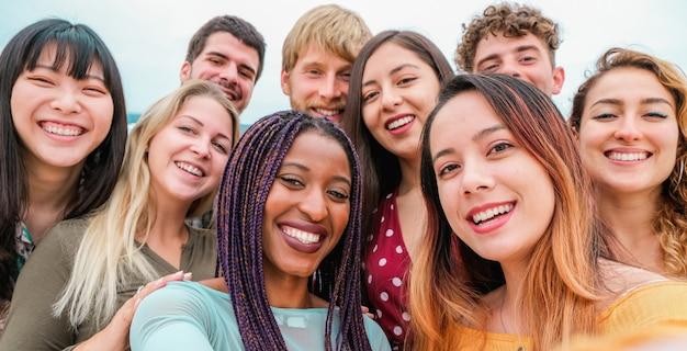 Jonge vrienden uit verschillende culturen en rassen die gelukkige gezichten fotograferen - jeugd, millenniumgeneratie en vriendschapsconcept met studenten die samen plezier hebben - focus op close-upmeisjes Premium Foto