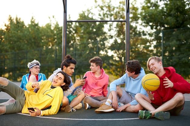 Jonge vrienden zittend op een basketbalveld, ontspannen en pauze nemen na de wedstrijd Premium Foto