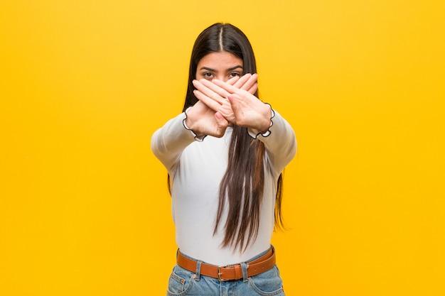 Jonge vrij arabische vrouw tegen een geel die een ontkenningsgebaar doet Premium Foto