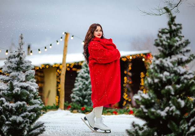 Jonge vrij donkerbruine vrouw die in rode lange laag bij de open ijsbaan schaatsen. kerst achtergrond. Premium Foto