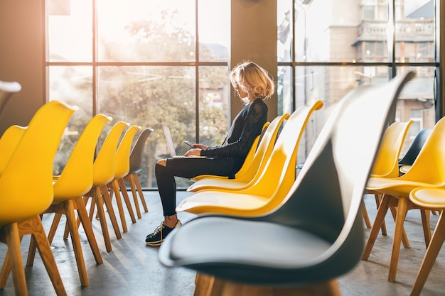 Jonge vrij drukke vrouw zit alleen in de vergaderruimte Gratis Foto
