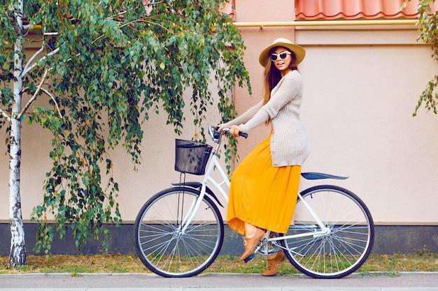 Jonge vrij mooie vrouw haar witte retro hipster fiets rijden, stijlvolle vintage kleding zonnebril en strooien hoed dragen, mode herfst herfst portret van elegante dame plezier buiten. Gratis Foto