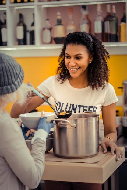 Jonge vrijwilliger. vrolijke aardige vrouw die de soep geeft terwijl ze in het vrijwilligerscentrum werkt Premium Foto