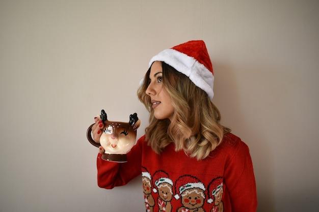 Jonge vrolijke blanke vrouw in een schattige rode kerst outfit en kerstmuts warme chocolademelk drinken Gratis Foto