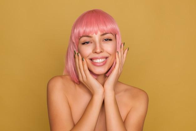 Jonge vrolijke blauwogige rozeharige dame met kort trendy kapsel die positief kijkt met een charmante glimlach en zachtjes gezicht met opgeheven handen aanraakt, geïsoleerd over mosterdmuur Gratis Foto