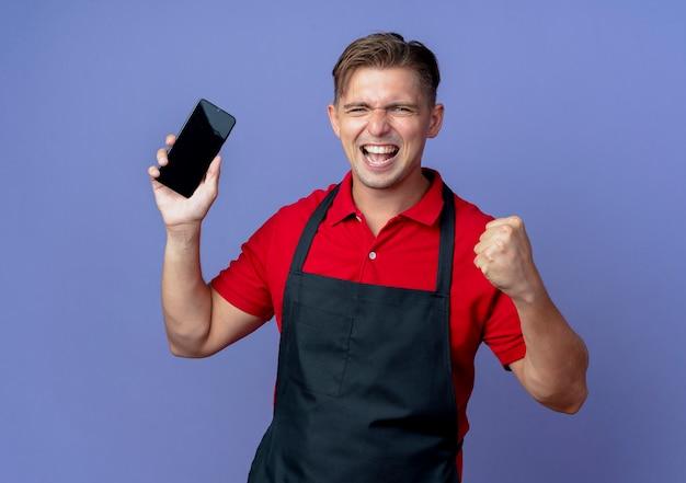 Jonge vrolijke blonde mannelijke kapper in uniform houdt telefoon vast en houdt vuist geïsoleerd op violette ruimte met kopie ruimte Gratis Foto
