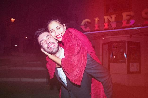 Jonge vrolijke kerel die op achter mooie glimlachende dame houden bij nacht Gratis Foto