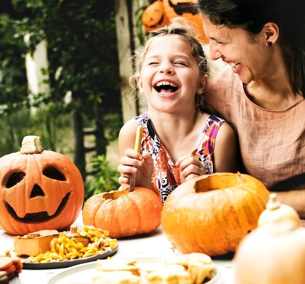 Jonge vrolijke meisjes snijdende pompoenen met haar mamma Premium Foto