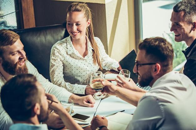 Jonge vrolijke mensen glimlachen en gebaar terwijl u ontspant in pub Gratis Foto