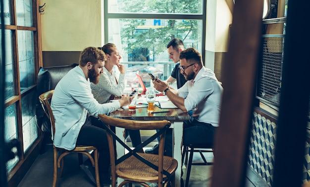 Jonge vrolijke mensen glimlachen en gebaar terwijl u ontspant in pub. Gratis Foto