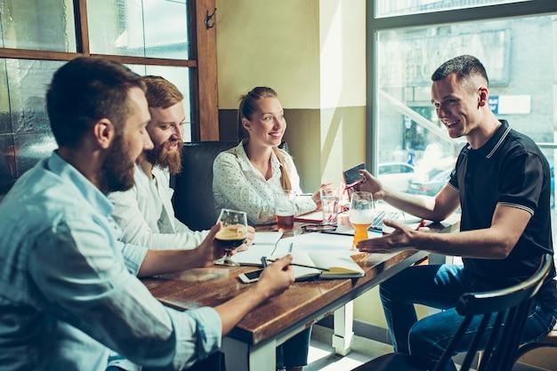 Jonge vrolijke mensen glimlachend en ontspannen in pub. Gratis Foto