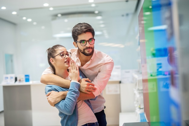 Jonge vrolijke paar in elektronische winkel. vriendin overtuigt haar vriend om bij haar nieuwe tv voor hun huis te zijn. Premium Foto