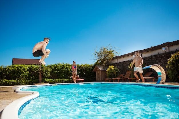 Jonge vrolijke vrienden glimlachen, ontspannen, springen in het zwembad Gratis Foto