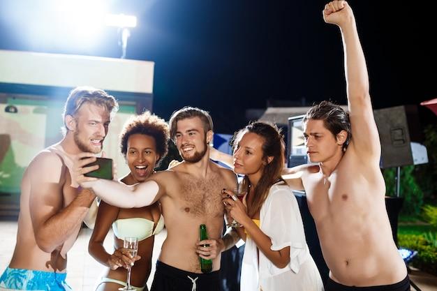 Jonge vrolijke vrienden glimlachen, vreugde, selfie maken, rustend op feestje Gratis Foto