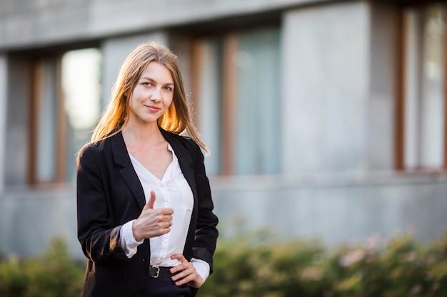 Jonge vrolijke vrouw die duim toont Gratis Foto