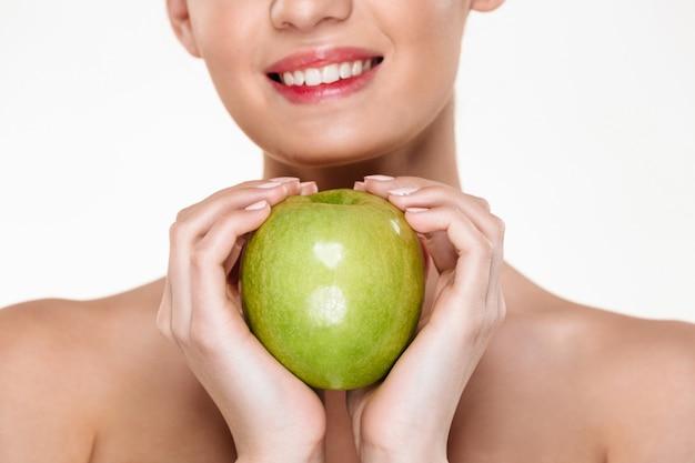 Jonge vrolijke vrouw met grote groene appel in beide handen zoals hartvorm Gratis Foto