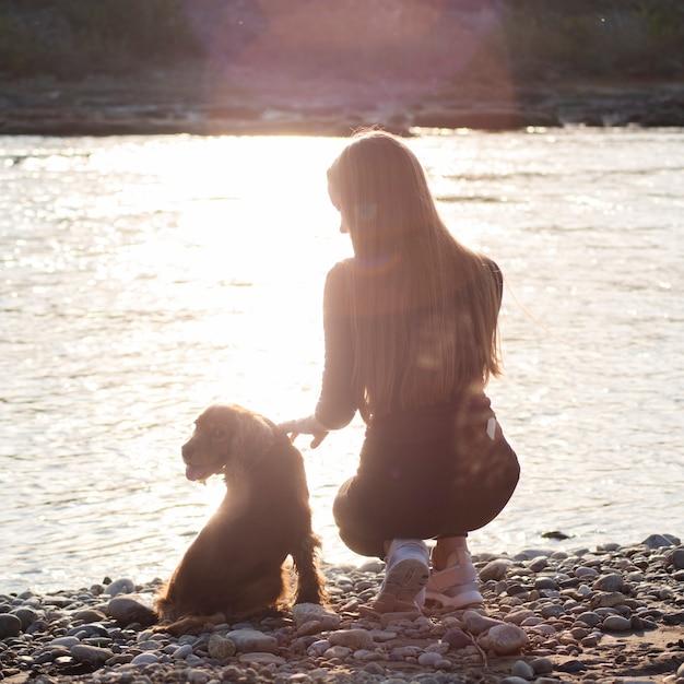 Jonge vrouw aan het meer met haar hond Gratis Foto