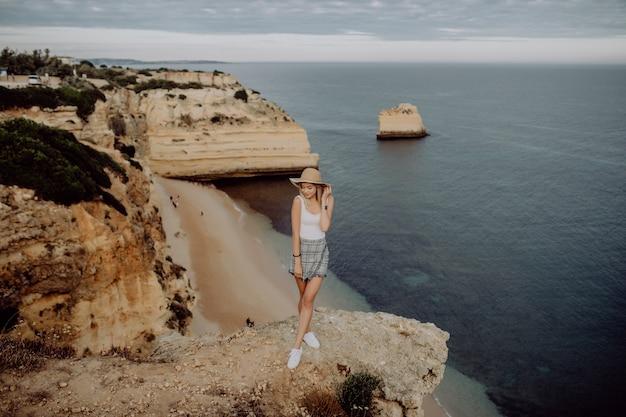 Jonge vrouw adembenemend uitzicht terwijl staande op de rand van de bergtop bewonderen Gratis Foto