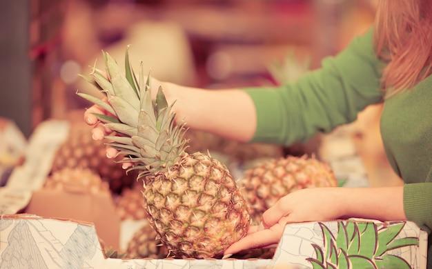 Jonge vrouw ananas kopen in een supermarkt. Premium Foto