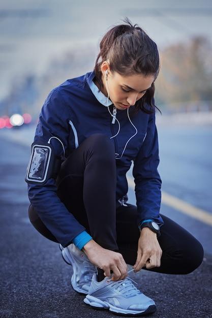 Jonge vrouw atleet met koptelefoon luisteren naar muziek en veters binden op straat Premium Foto